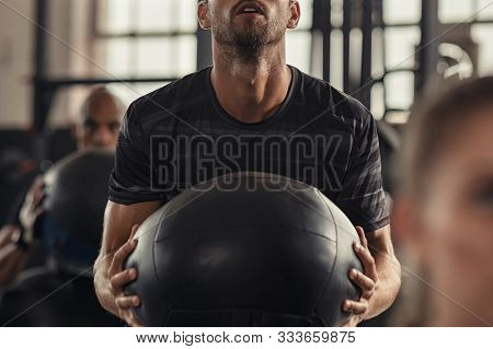 Closeup of sportsman doing weight lifting with heavy medicine ball. Determined man doing training in fitness center. Young man doing intensive squat workout at gym with fitness ball.