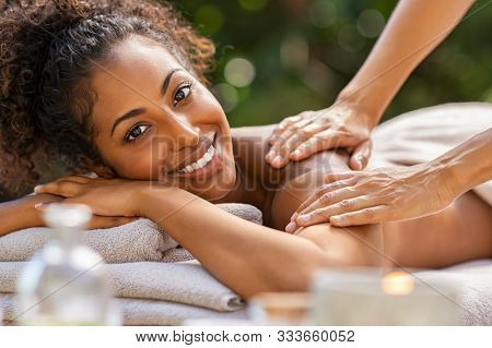 Happy woman relaxing with oil massage on her back at spa resort. Portrait of young african woman receiving back massage, looking at camera. Closeup face of smiling girl relaxing during body treatment.