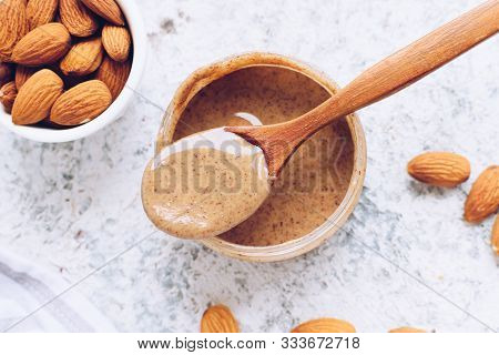 Almond Nut Butter In Glass Jar. Homemade Raw Organic Almond Nuts Paste On Grey Background. Healthy N