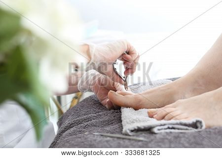 Pedicure. The Beautician Performs A Pedicure Treatment. Bare Feet On A Gray Towel During Care Treatm