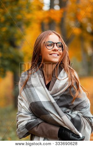Happy Young Hipster Woman With A Positive Smile In A Stylish Knitted Scarf In A Coat In Trendy Glass