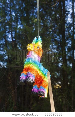 A Colorful Pinata In The Shape Of A Goat Hanging From The Tree