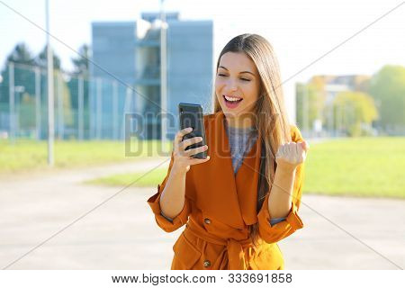 Success Woman Celebrating Outdoor Cheering And Raising Her Fist Up In Exultation. Excited Fashion Wo