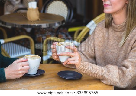 Two Beautiful Young Women Friends Having Coffee In A Cozy Street Coffee Shop, Chatting And Laughing.