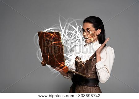 Shocked Steampunk Woman In Glasses Using Vintage Laptop With Glowing Fairy Illustration Isolated On