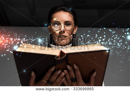Low Angle View Of Steampunk Woman In Glasses Reading Book With Glowing Illustration Above