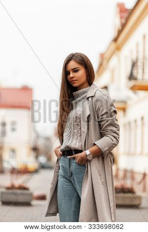 Fashionable Pretty Young Woman In Jeans In A Trendy Knitted Sweater In A Stylish Beige Trench Coat W