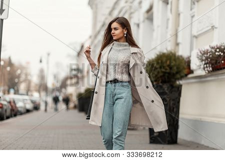 Model Of A Young Beautiful Woman In A Fashion Trench Coat In A Stylish Knitted Sweater With A Leathe