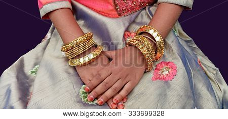 Bangles Fancy Designs On A Girls Hands. Beautiful Elegant Patterns In Gold Plated Material.  Glitter