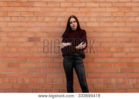 European Pretty Young Fashionable Woman In A Stylish Knitted Burgundy Sweater In Trendy Black Leathe