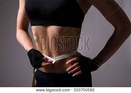Close Up Of Sporty Woman With Muscular Body Measuring Her Waistline Over Gray Background