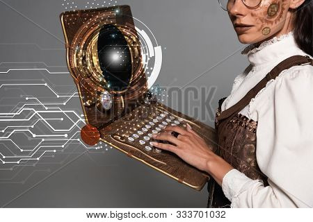Cropped View Of Steampunk Woman Using Vintage Laptop With Glowing Digital Illustration Isolated On G