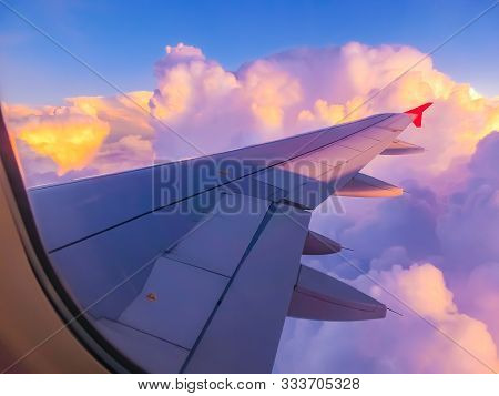 View From An Airplane On A Blue Sky And White Clouds. Flying On The Airplane. Wing Of Airplane Flyin