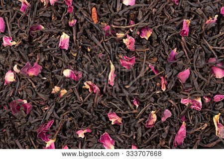 Earl grey black dry tea leaves with rose petals background