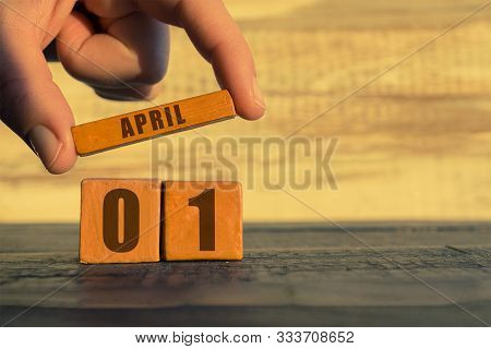 April 1st. Day 1 Of Month, Calendar On A Wooden Cube. A Womans Hand Puts The Name Of The Month On Th