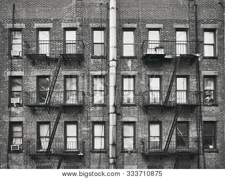 Black And White Picture Of An Old Brick House With Fire Escapes, New York, Usa.