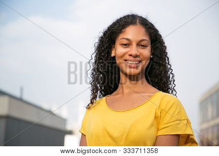 Attractive Young Woman Smiling At Camera. Portrait Of Beautiful Cheerful Young Woman In Yellow T-shi