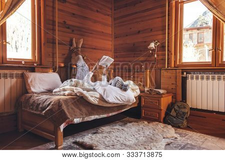 Young girl relaxing and reading book on cozy bed in log cabin in winter