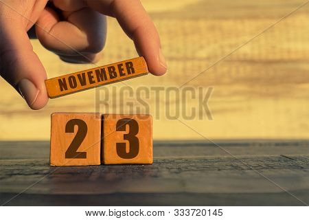 November 23rd. Day 23 Of Month, Calendar On A Wooden Cube. A Womans Hand Puts The Name Of The Month