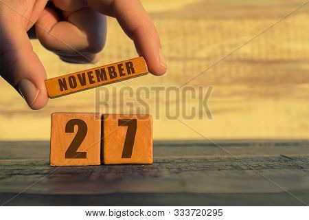 November 27th. Day 27 Of Month, Calendar On A Wooden Cube. A Womans Hand Puts The Name Of The Month