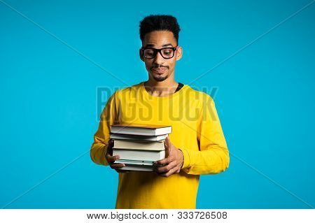 African Student Is Dissatisfied With Amount Of Homework And Books. Man In Glasses, He Is Annoyed, Di