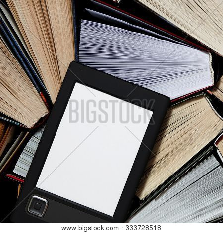 The E-book With A White Screen Lies On The Open Multi-colored Books That Lie On A Dark Background, C