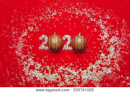 Christmas Card With The Inscription 2020 Of Sparkles And Balls. Red Background, Gold Decorations For