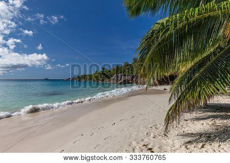 Paradise Beach With White Sand, Palms, Rocks, Turqoise Water On Seychelles Island Praslin
