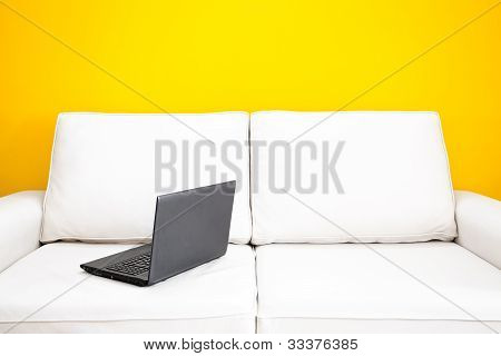 White Sofa And Laptop Against A Yellow Wall In The Apartment