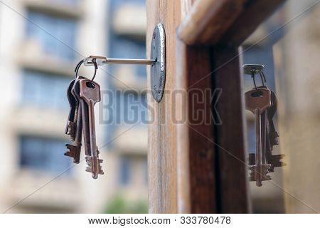 Set Os Old Keys In The Keyhole Reflecting On The Glass Of Door Frame, Blurred Building Background