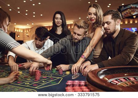Happy People Are Betting In Gambling At Roulette Poker In A Casino