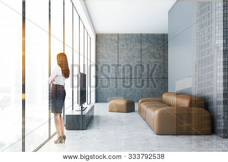 Young Woman With Black Hair Standing In Panoramic Living Room With Gray And Concrete Walls, Comforta
