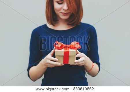 A Girl With Short Red Hair In A Blue Jumper Holds A Gift Tied With A Red Satin Ribbon. Portrait Of A