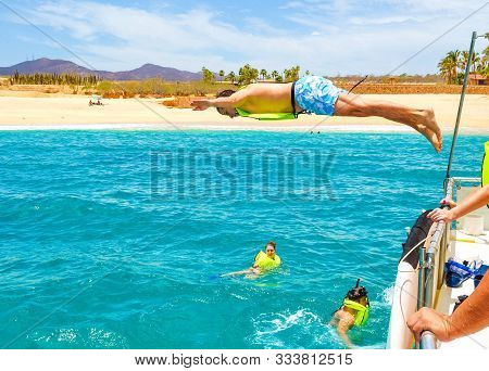 Young Man With Life Saving Vest Jumping In The Pacific Ocean In Cabo San Lucas, Baja California, Mex