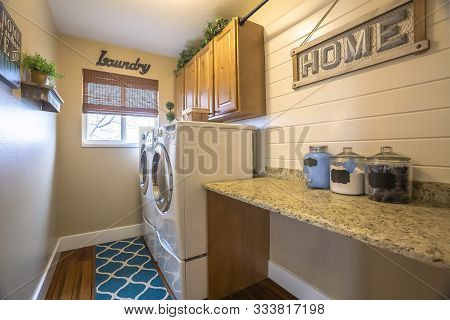 Laundry Room Of A Home With Washing Machine Against The Wall And Small Window