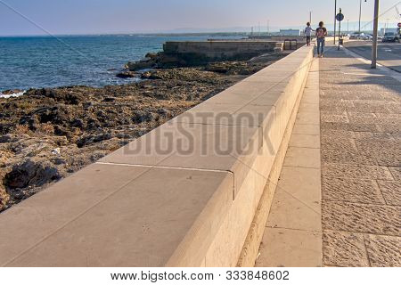 Young Blonde Kid Walking On A Parapet Along The Sea And Holding His Mother Hand On A Sunny Day On Th