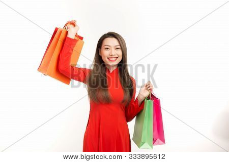 Happy Asian woman holding shopping bags and wearing Ao Dai Vietnam. Isolated on white background poster