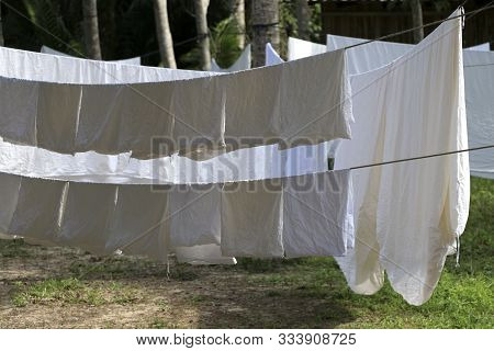 The white cloth is exposed to the sun on the clothesline. A large white cloth hung on a clothesline. poster