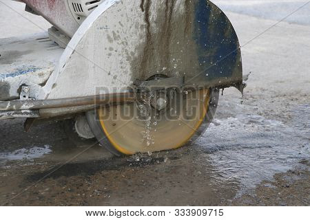 Concrete Cutting Machine Are Cutting Concrete Floor Using Cast Water To Reduce Dust Spread.