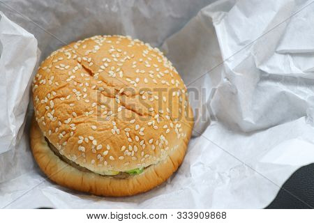The Hamburger Is Placed On White Paper. Hamburger With White Sesame Sprinkled On Top.