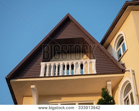Balcony On The Top Floor With White Balusters Against The Blue Sky