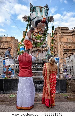 Madurai, India - August 23, 2018: A Couple Praying In Front Of Nandi Statue. Nandi Is The Sacred Bul