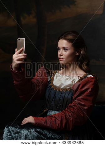 Old And New, Concept. Beautiful Young Renaissance Style Woman Taking Selfie On Phone. Beautiful Myst