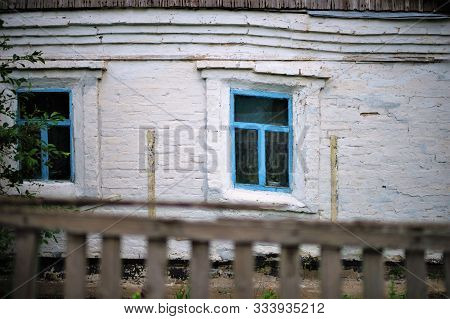 Facade Of An Old Rural House With Blue Window Frames. Old Deformation Of The Wall Structure Caused B