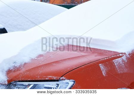 Snowy. Car Covered With Snow. Winter Problems Of Car Drivers. Clearing Orange Car From Snow.