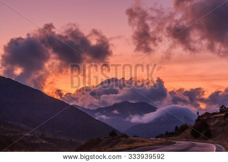 Red Sunset In The Mountains With Big White Clouds. Clouds Concept