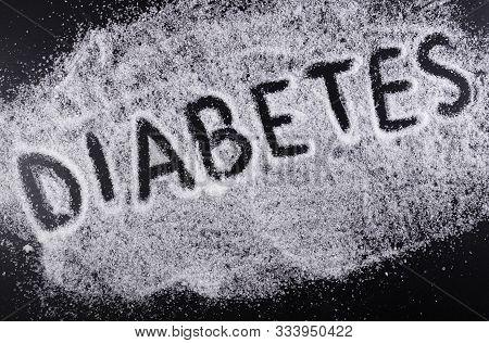 The Word Diabetes On The Spilled Sugar On Black Background. Harm Of Sugar, Diabetes Disease Medical