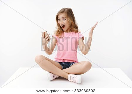 Excited happy cute teenage girl little bloger, thrilled see lots followers, raise hand cheerful amused, smiling broadly, hold smartphone, look mobile phone screen enthusiastic, white background poster