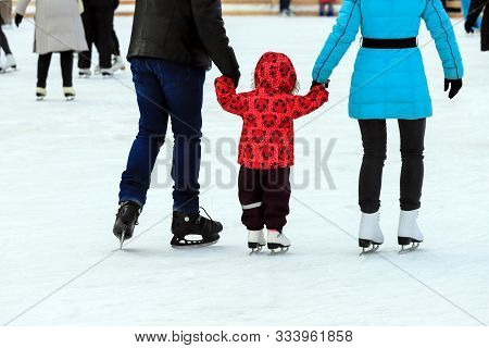 A Little Boy With His Parents Skates On The Ice Rink In The Winter. A Man And Woman Is Teaching Her