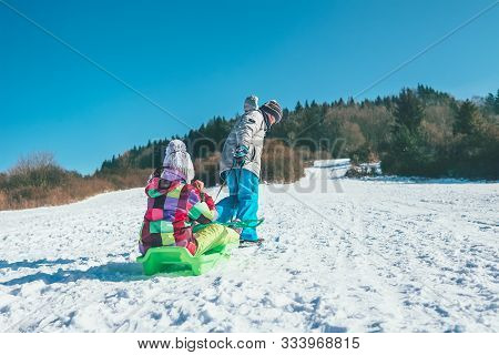 Little Boy Carrying Girl In The Sled And Enjoying Winter Sledding Time. Funny Winter Holidays Spendi